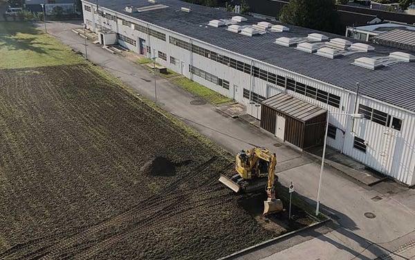 Ein Bagger verdichtet die Erde vor dem Logistikzentrum von klarx