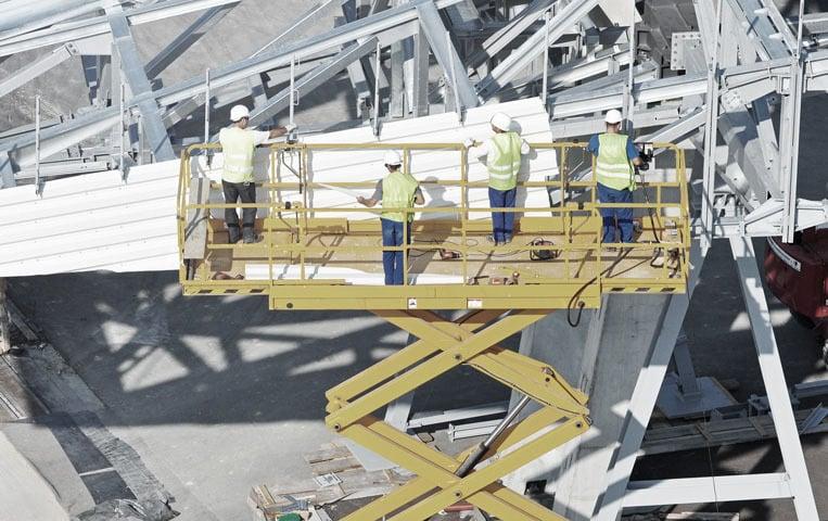 Arbeiter stehen auf einer Arbeitsbühne auf der Baustelle