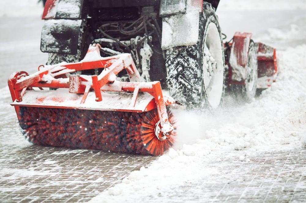 Eine Baumaschine räumt den Schnee auf den Straßen